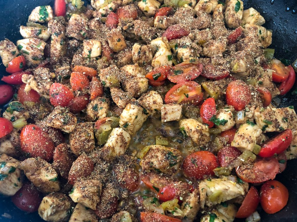 Cilantro, tomatoes, diced green chilies, and the rest of the spic blend has been added to the chicken and onions in the cast iron skillet.
