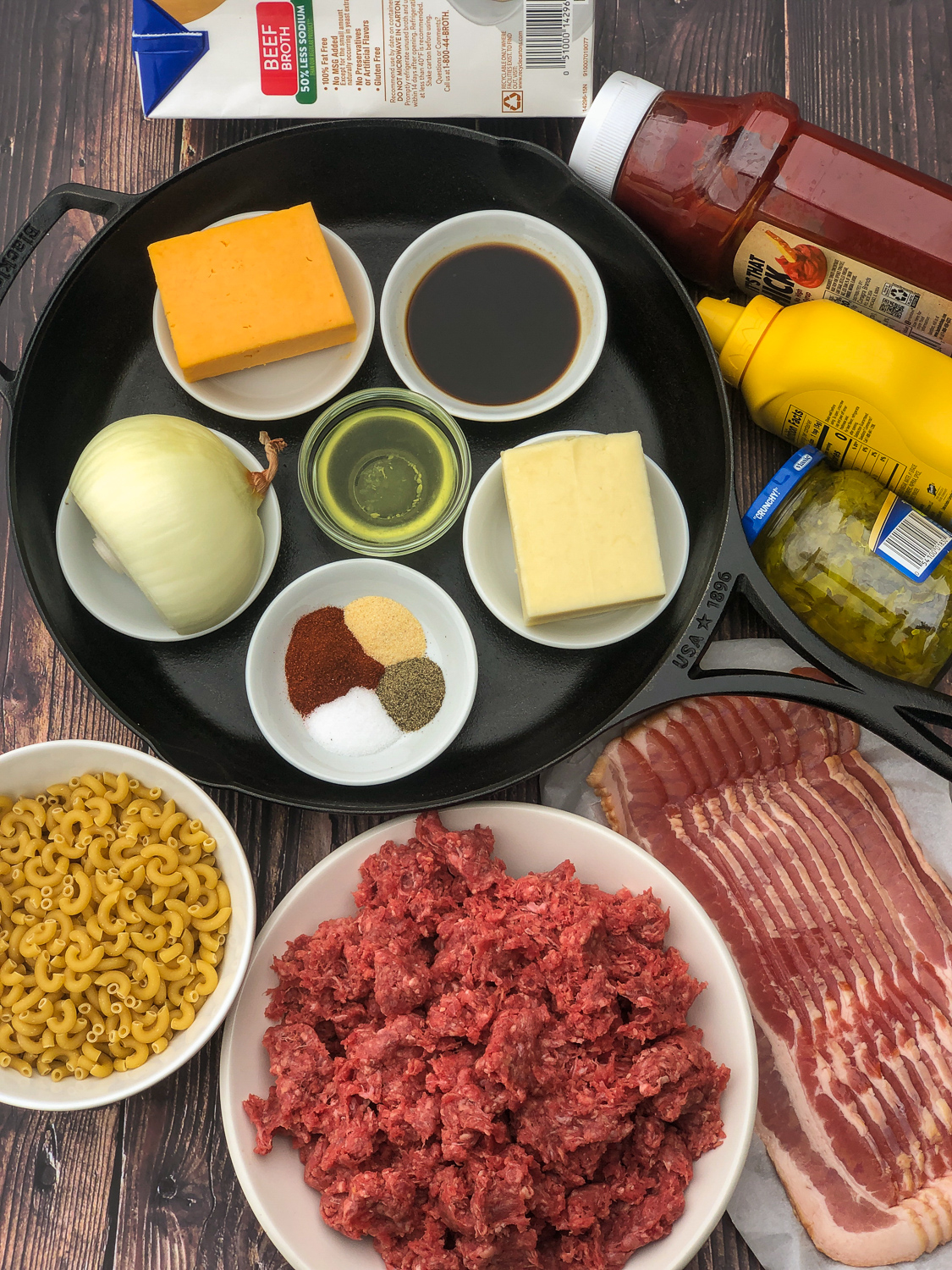 Ingredient to make Bacon Cheeseburger Casserole in a cast iron skillet: cheddar cheese, worcestershire sauce, mozzarella cheese, dill pickle juice, spices, onion, macaroni, ground beef, bacon, dill pickle relish, yellow mustard, ketchup, and beef broth.