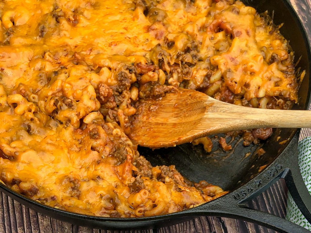 Cast iron skillet of bacon cheeseburger casserole with a large portion missing and a wooden spoon in to serve.