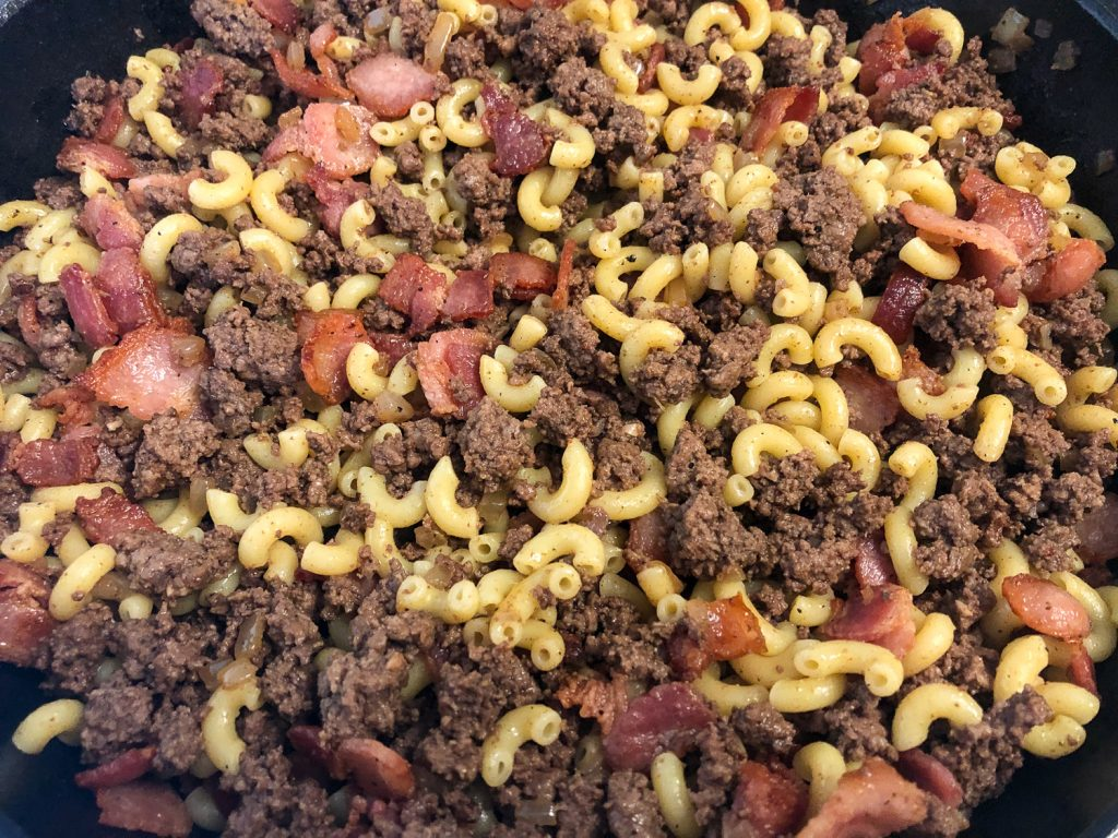 Bacon, ground beef, and macaroni mixed together in a skillet.