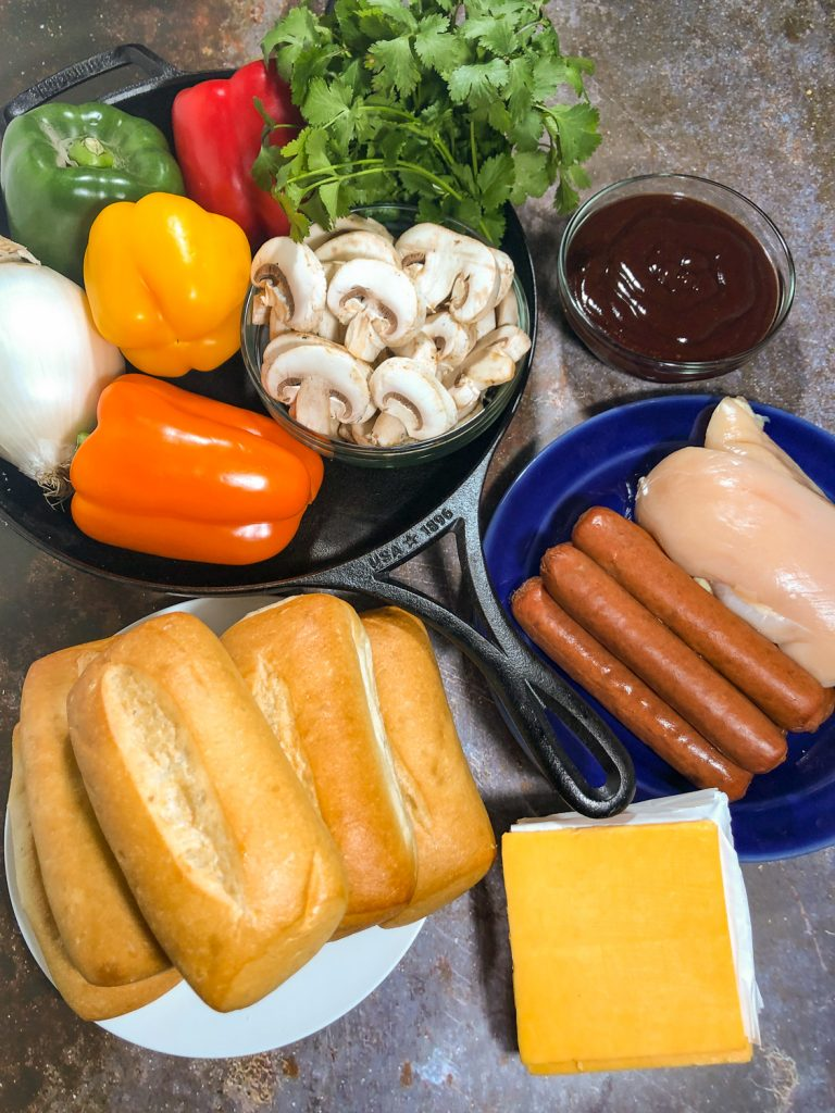 Ingredients for making Barbecue Chicken, smoked sausages, cheddar cheese slices, hoagie buns, bell peppers, onion, mushroom, cilantro, barbecue sauce, and a cast iron skillet.