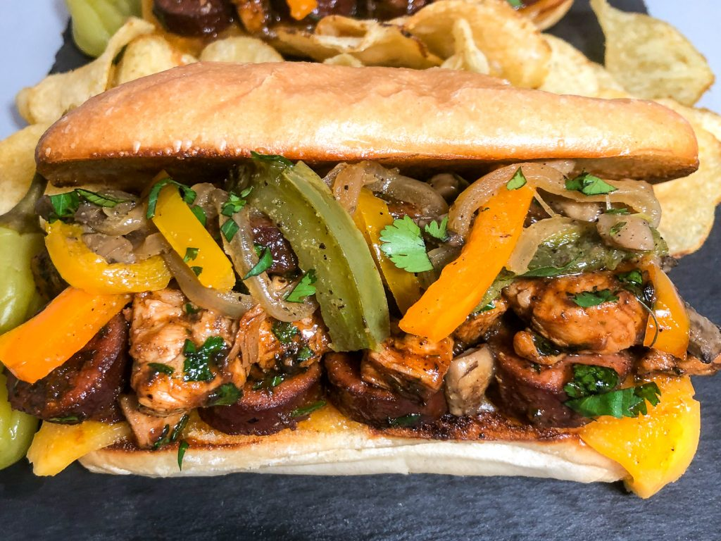 Horizontal image of a toasted cheese lined bun loaded with chicken, sausage, bell peppers, onions, mushroom in barbecue sauce and garnished with cilantro.