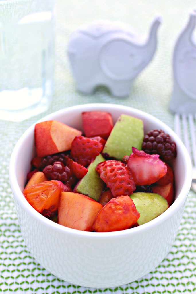 A small bowl of Fresh Fruit Salad with a glass of water in the background and white elephants from The Complete Savorist