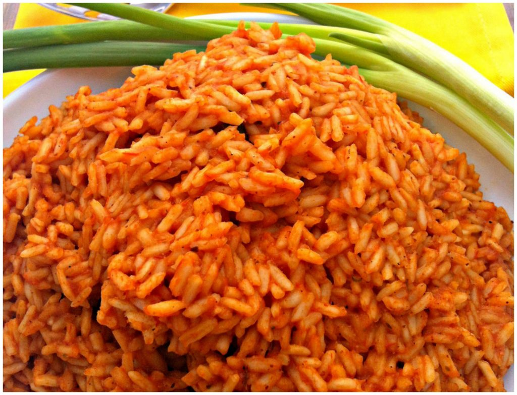 Spanish Rice on a white plate with green onions in the background from The Complete Savorist by Michelle De La Cerda