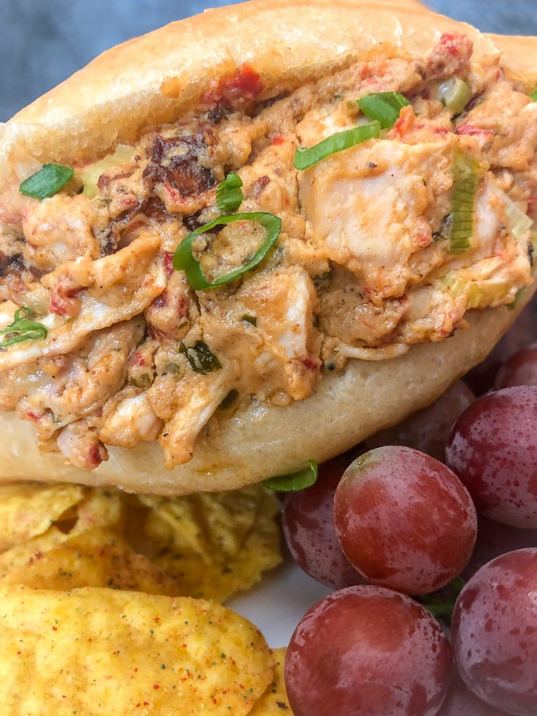 Close up of a chicken sandwiches made with leftover dip sitting on red grapes and tortilla chips.