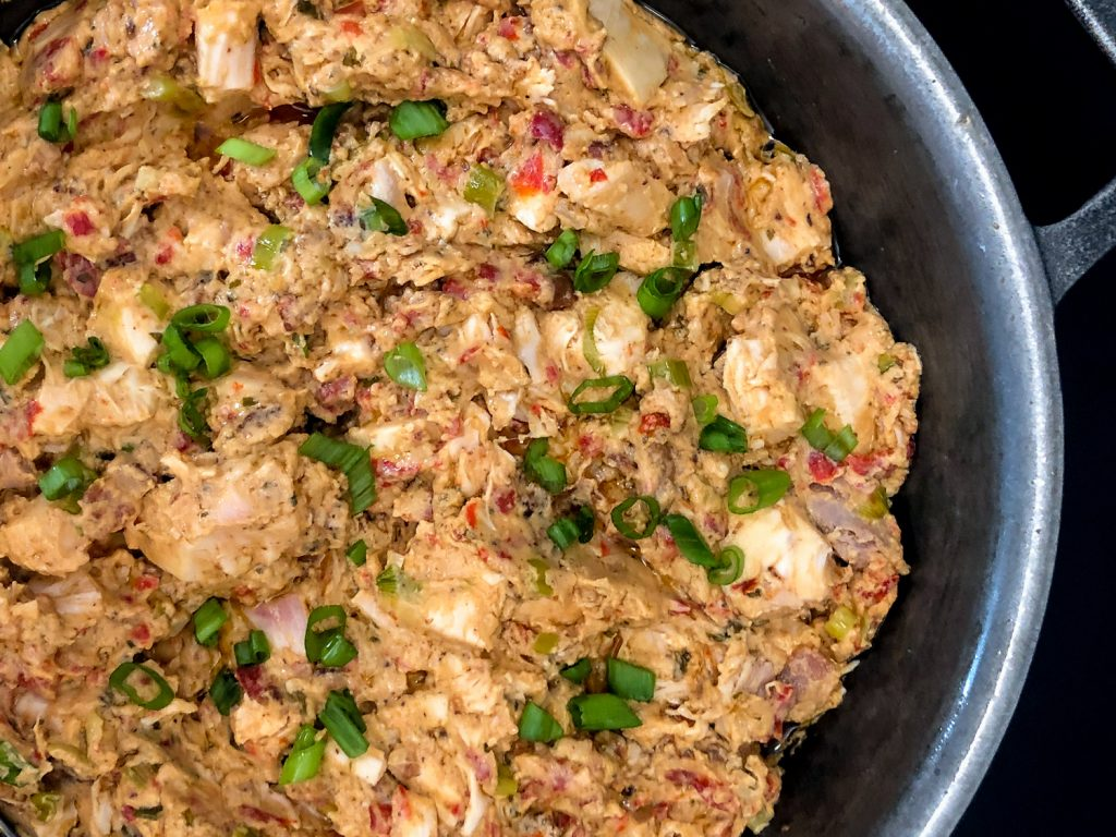 Skillet full or ready to serve Cheesy Red Pepper Chicken Sandwiches garnished with green onions.
