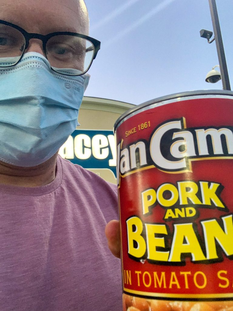 Dutch Oven Daddy wearing a mask holding a can of Van Camp's pork and beans.