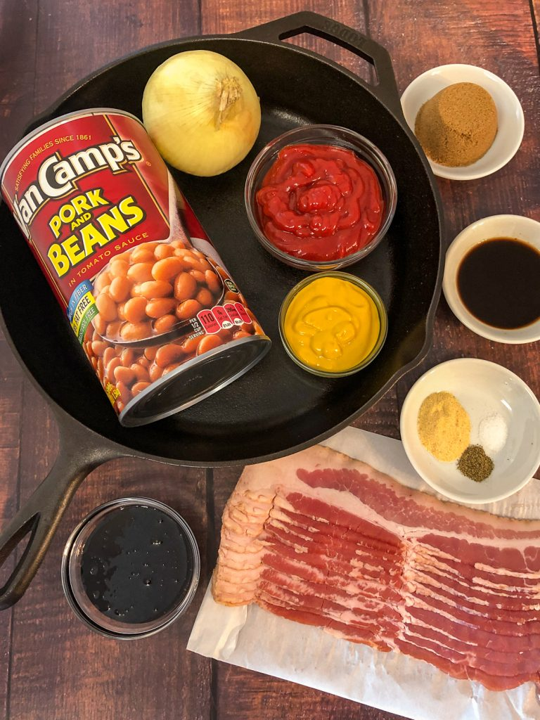 Ingredients to make Southern style baked beans: dark brown sugar, Worcestershire sauce, seasonings, bacon, molasses, pork and beans, onion, ketchup, and mustard with a cast iron skillet.