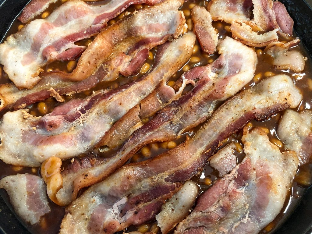 Slices of partially cooked bacon is placed atop the mixed beans in the skillet.