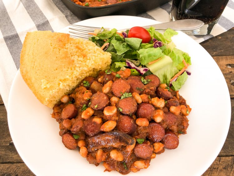 Cornbread, salad, and beans n franks on a white plate, a glass of soda and the skillet nearly out of frame.