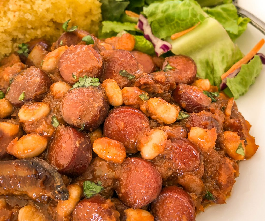 Close up image of beanie weenies on a white plate, salad and cornbread in the background.