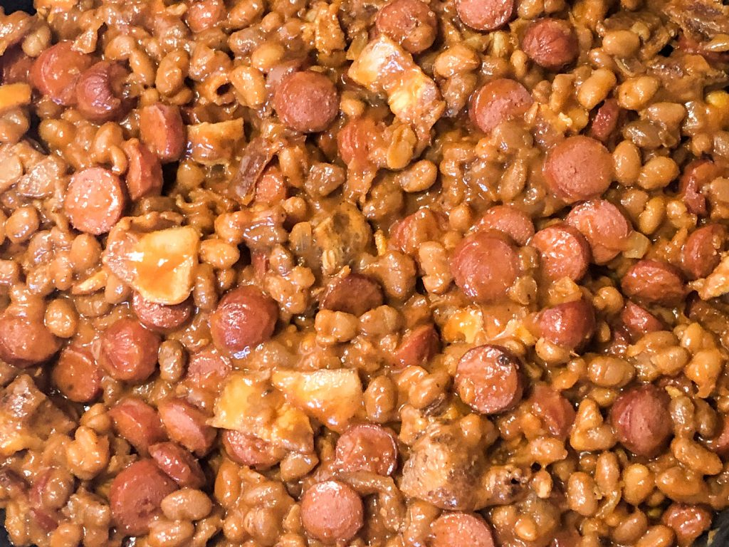 Baked beans with bacon have been added to sliced hot dogs in the skillet.