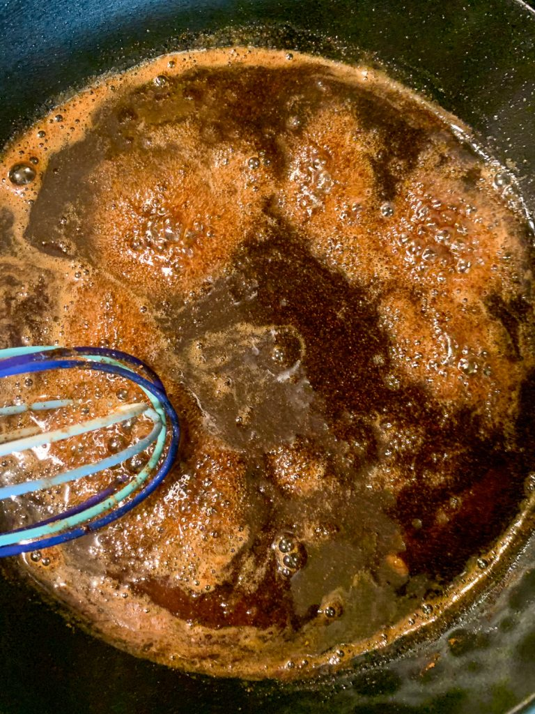 The sauce for bananas foster is being made in a cast iron skillet; a whisk is being used during the high simmer.