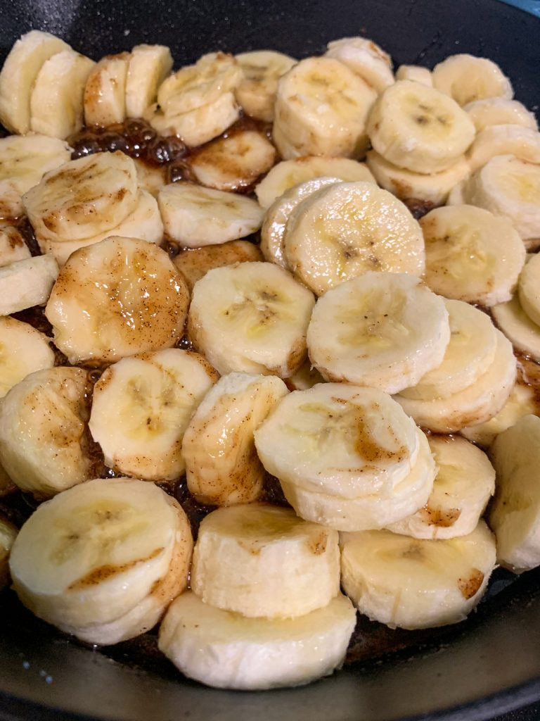 Coin-sliced bananas have been added to sugary sauce.