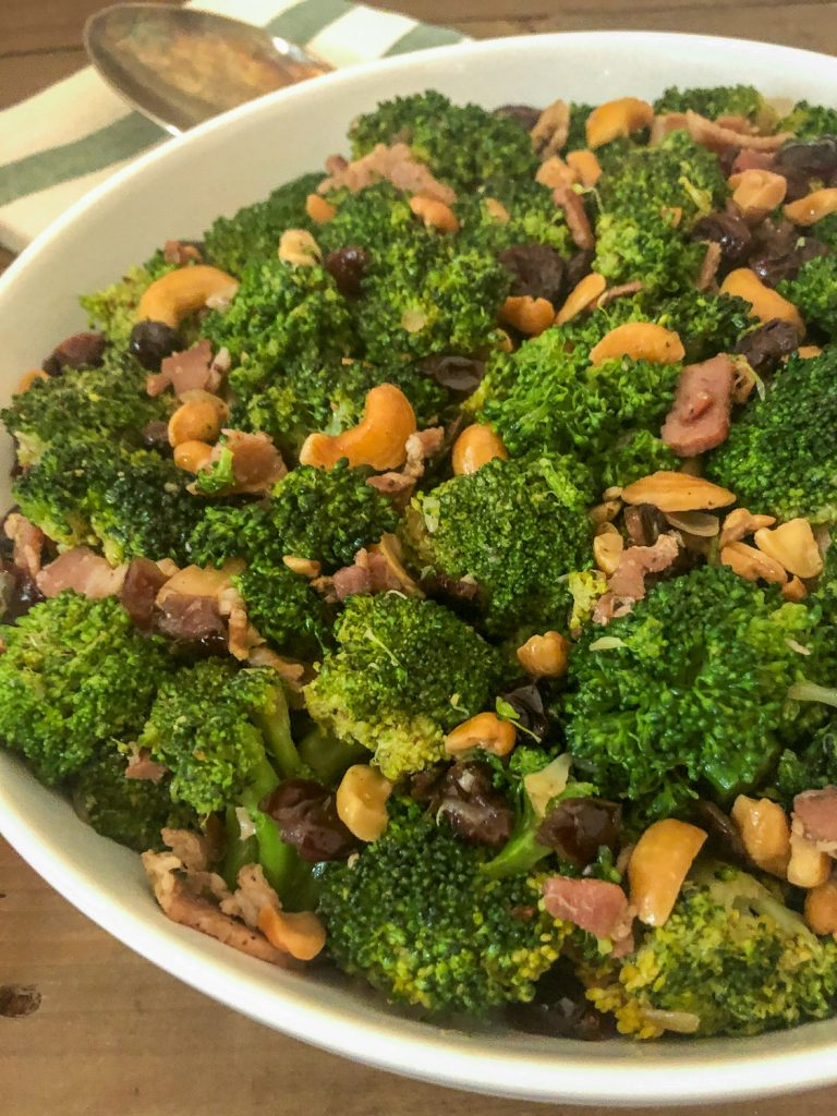 Side view of cranberry cashew broccoli in a white bowl.