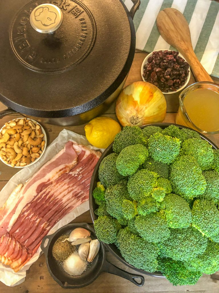 Ingredients to make the side dish: dried cranberries, onion, lemon, broth, broccoli, bacon, cashews, and herbs/spices along with the Dutch oven and a wooden spoon on a green linen.
