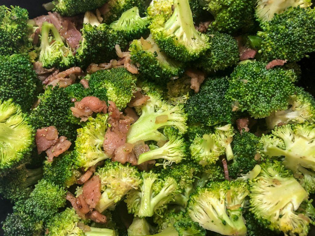 Broccoli has been added to the sautéed bacon and onions.