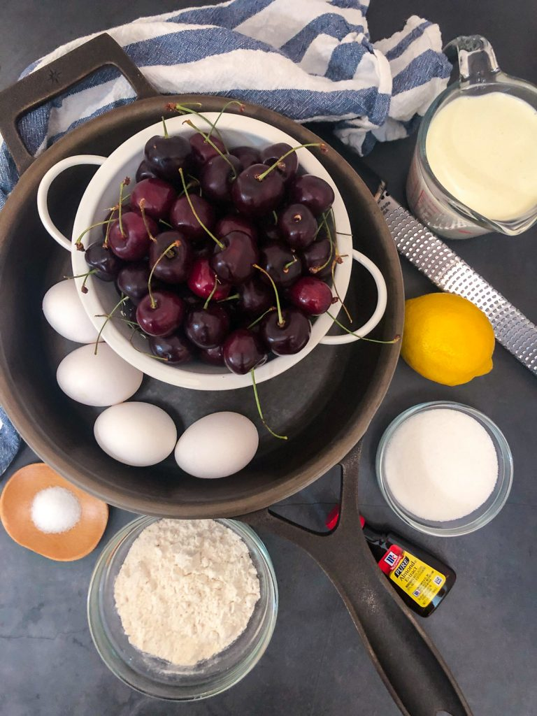 Ingredients needed to make the recipe in and around a cast iron skillet: salt, flour, almond extract, sugar, lemon zest, cream, eggs, and fresh cherries