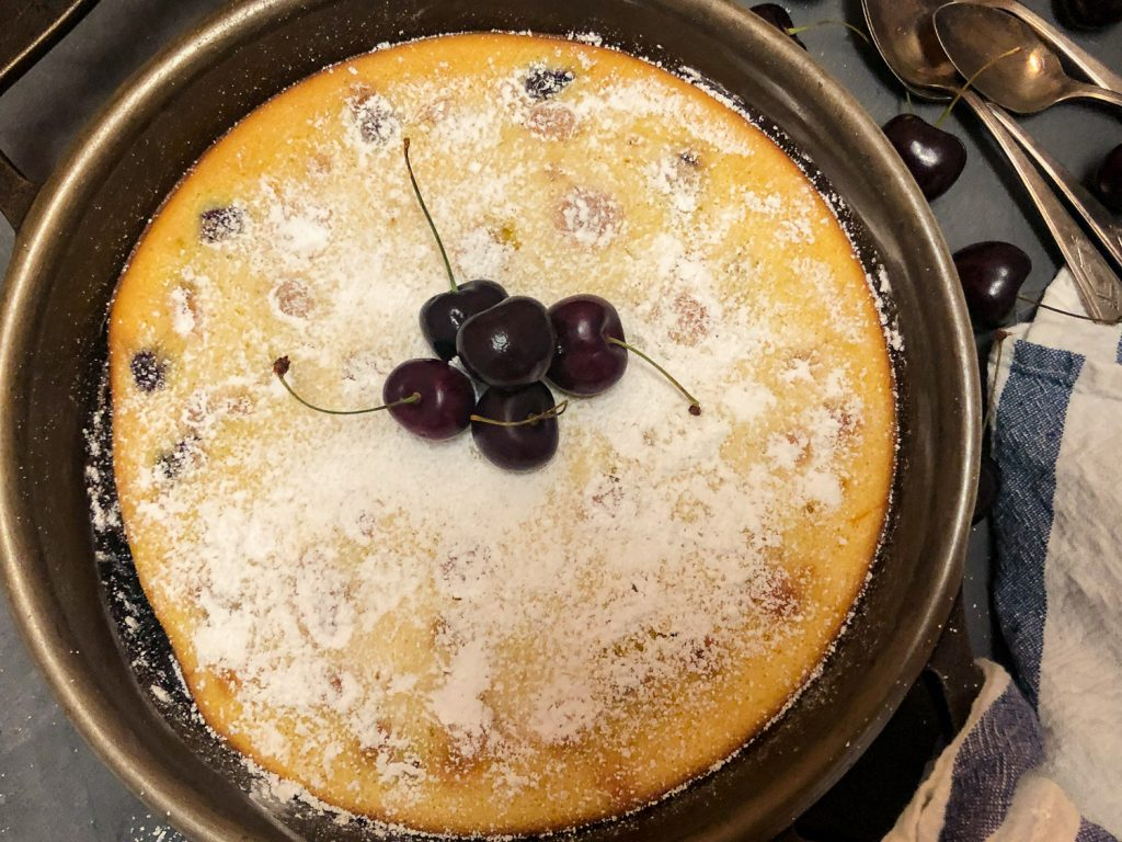 Skillet Cherry Clafoutis fresh from the oven, dusted with powdered sugar and garnished with fresh cherries.