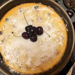 Cherry Clafoutis in a cast iron skillet dusted with powered sugar and garnished with fresh cherries.