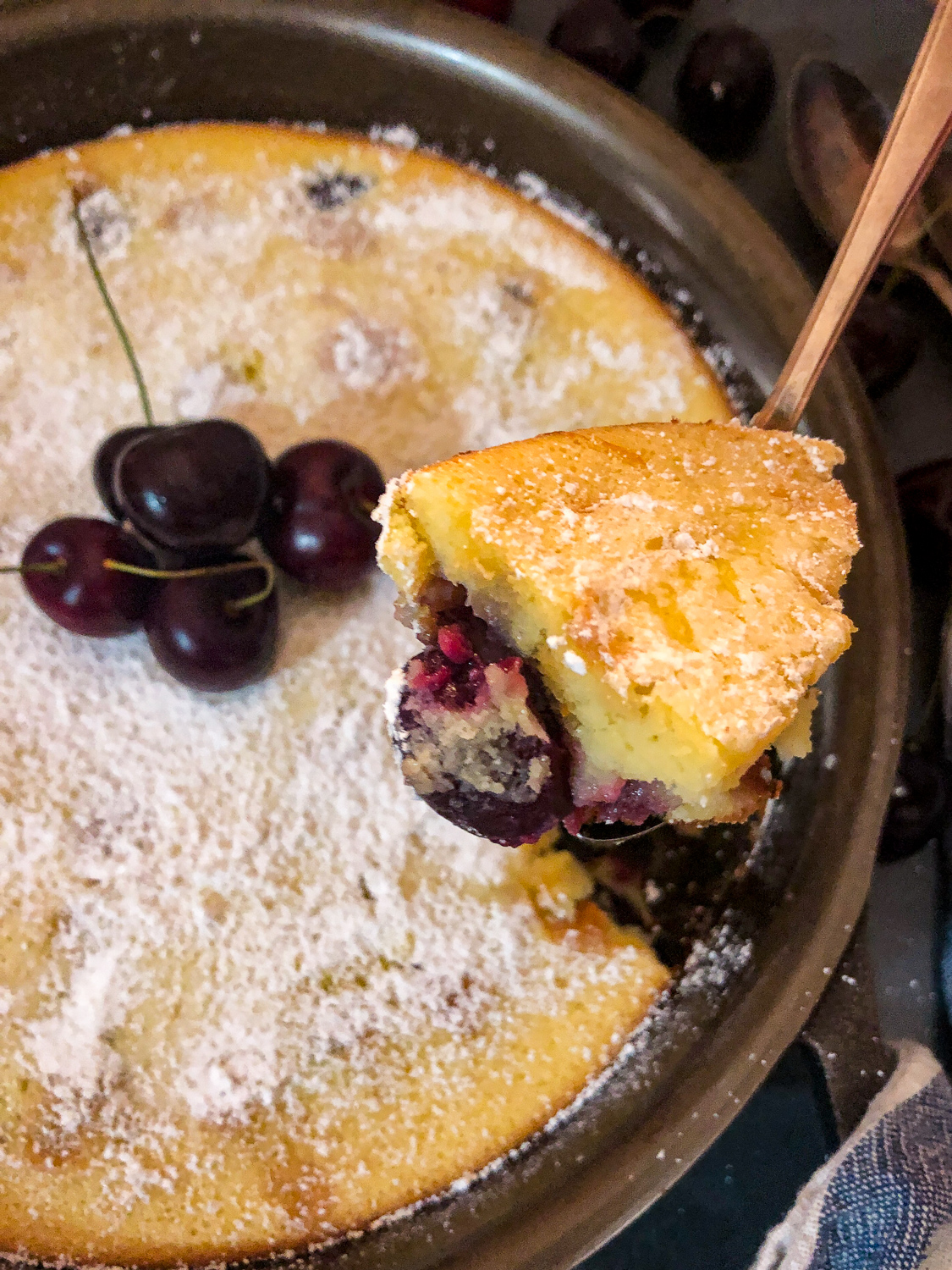 A bite of cherry clafoutis being removed from the skillet.