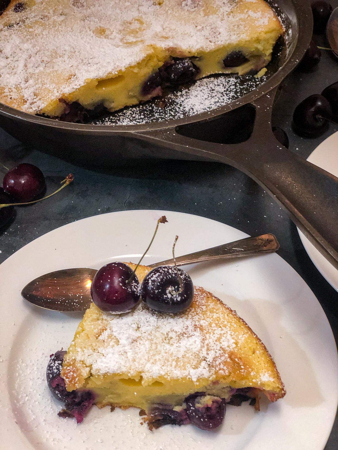 A slice of cherry clafoutis on a white plate and the remaining dessert still in the skillet.