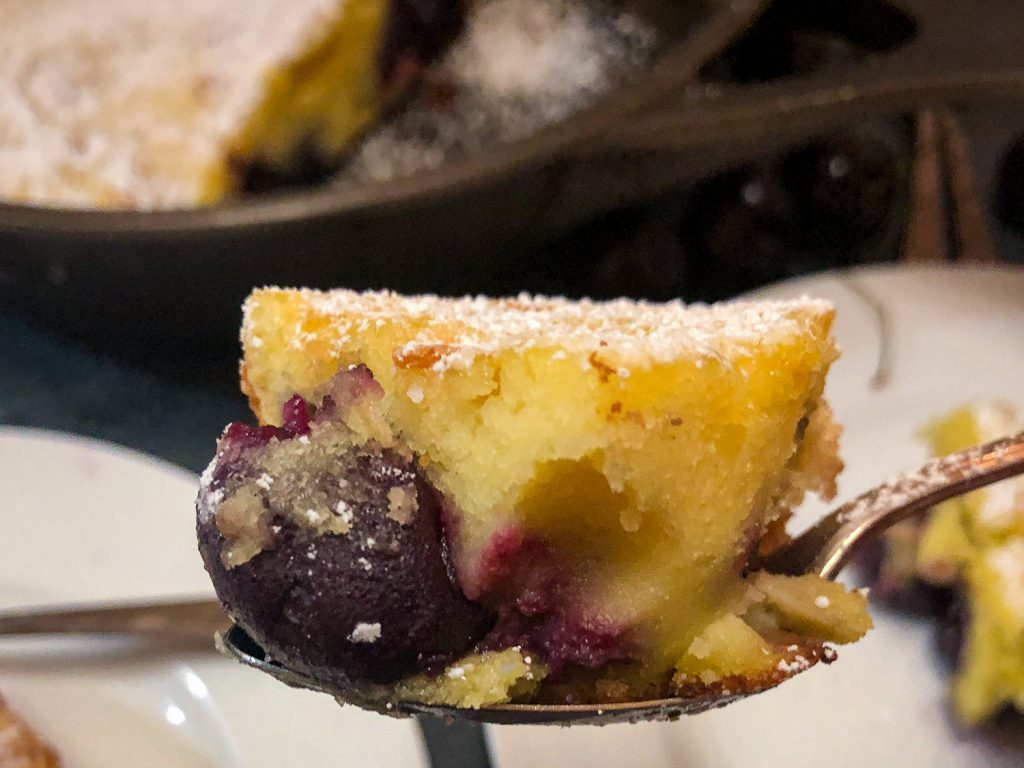 A bite of cherry clafoutis on a spoon to show the texture of the dessert.