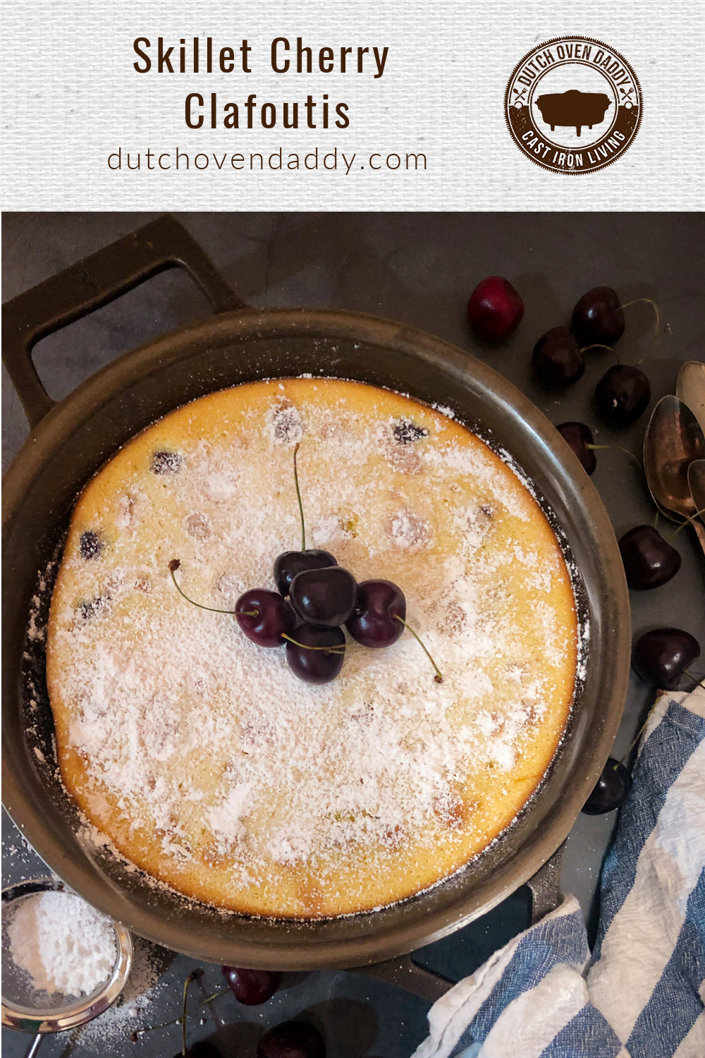 Cherry clafoutis in a cast iron skillet dusted with powdered sugar with fresh cherries as a garnish.