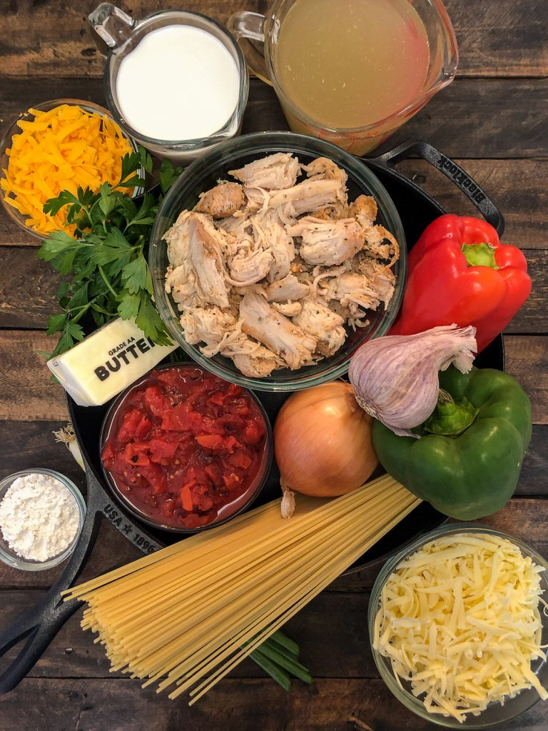 Ingredients needed to make chicken spaghetti in and around a cast iron skillet: cheddar cheese, cream, broth, chicken, parsley, butter, chicken, bell peppers, garlic, onions, diced canned tomatoes, flour, green onions, and white cheddar cheese.