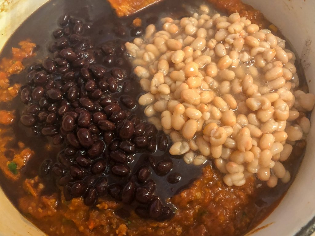 Cans of undrained black and white beans have been added to the chili.