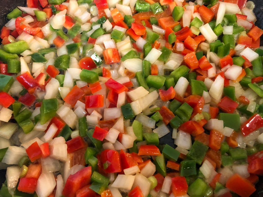 Diced onions and bell peppers sautéing in a cast iron skillet.