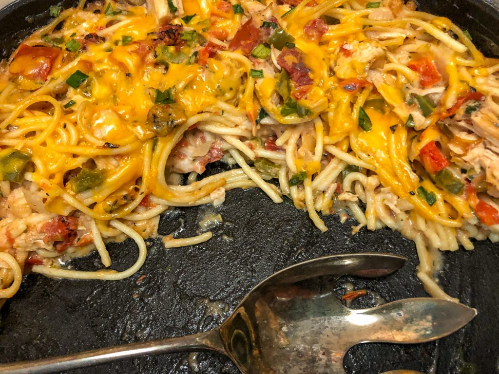 Cast iron skillet with a portion or two of chicken spaghetti left with a serving spoon.