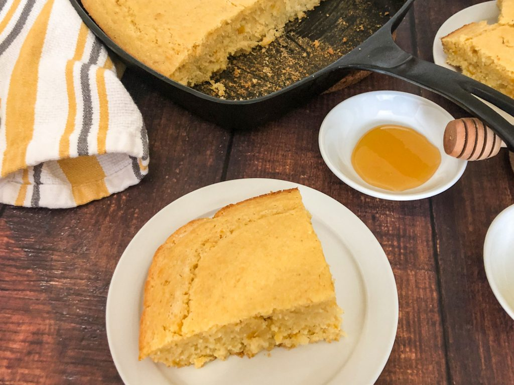 A large piece of cornbread on a white plate, the skillet in the background, a yellow and grey dish cloth near the skillet and honey off to the back right.