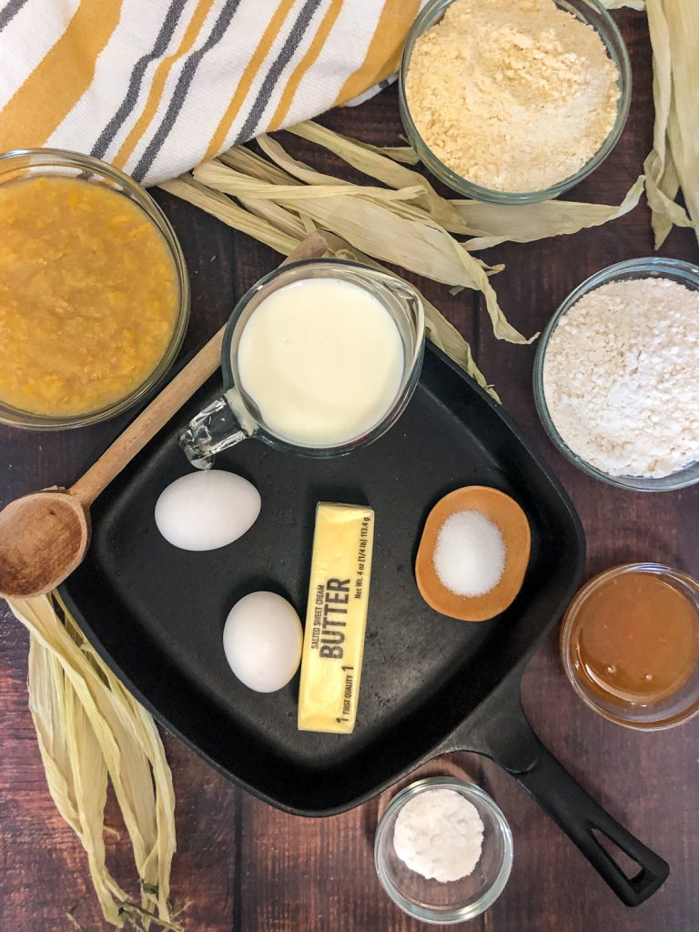 The individual ingredients needed to make Creamed corn cornbread in and around a square cast iron skillet: creamed corn, cornmeal, milk, flour, eggs, butter, salt, honey, and baking powder.
