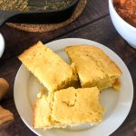 Three slices of cornbread on a white plate; a bowl of chili, honey, and the skillet are off to the sides going off image.