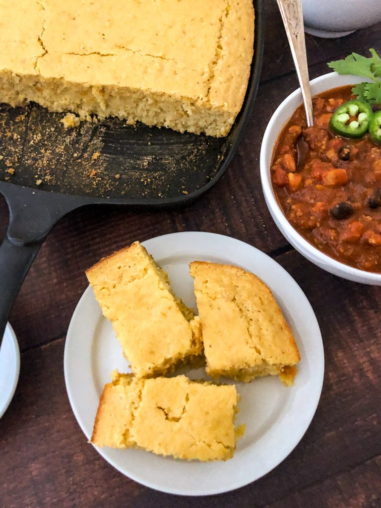 Three slices of cornbread on a white plate with a bowl of chili off to the right side and the skillet with the remaining unsliced cornbread off to the back left side.