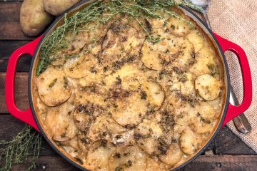 Skillet Scalloped Potato Gratin garnished with fresh thyme.