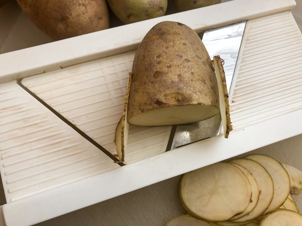 Half of a russet potato resting on a mandolin slicer, showing a slice of potato from both the thinner and thicker side of the blade.