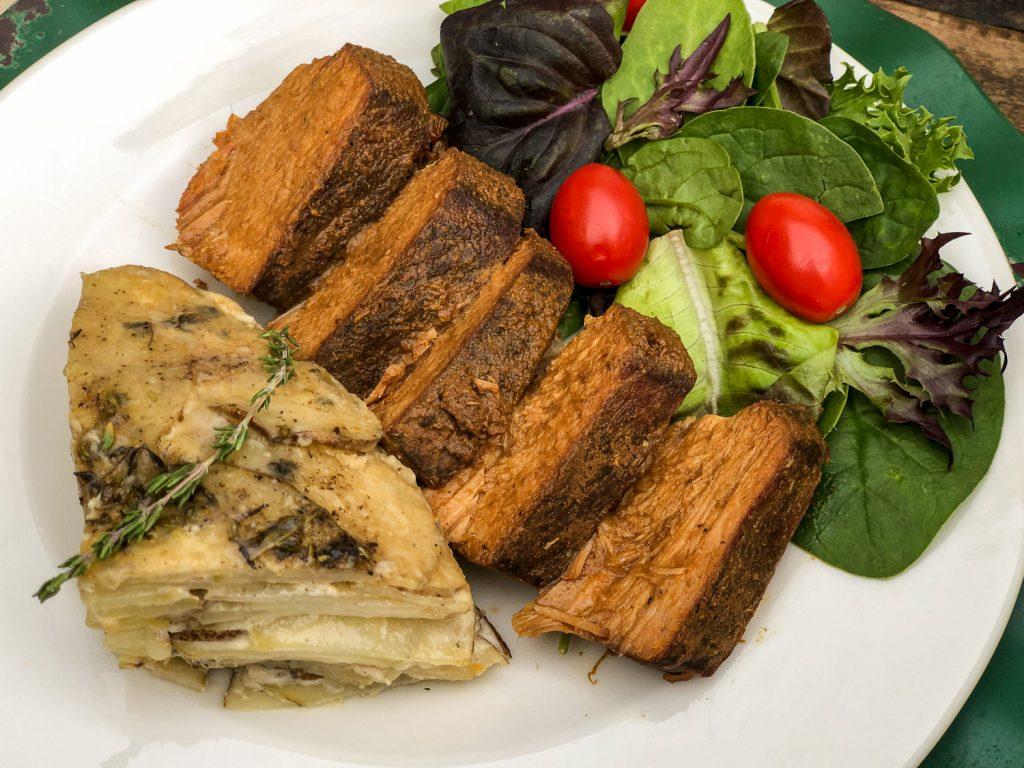 Potatoes plated with pork roast and a salt.