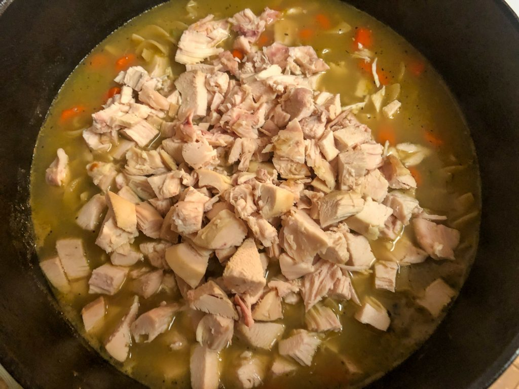 Cooked, cubed chicken being added to the soup.