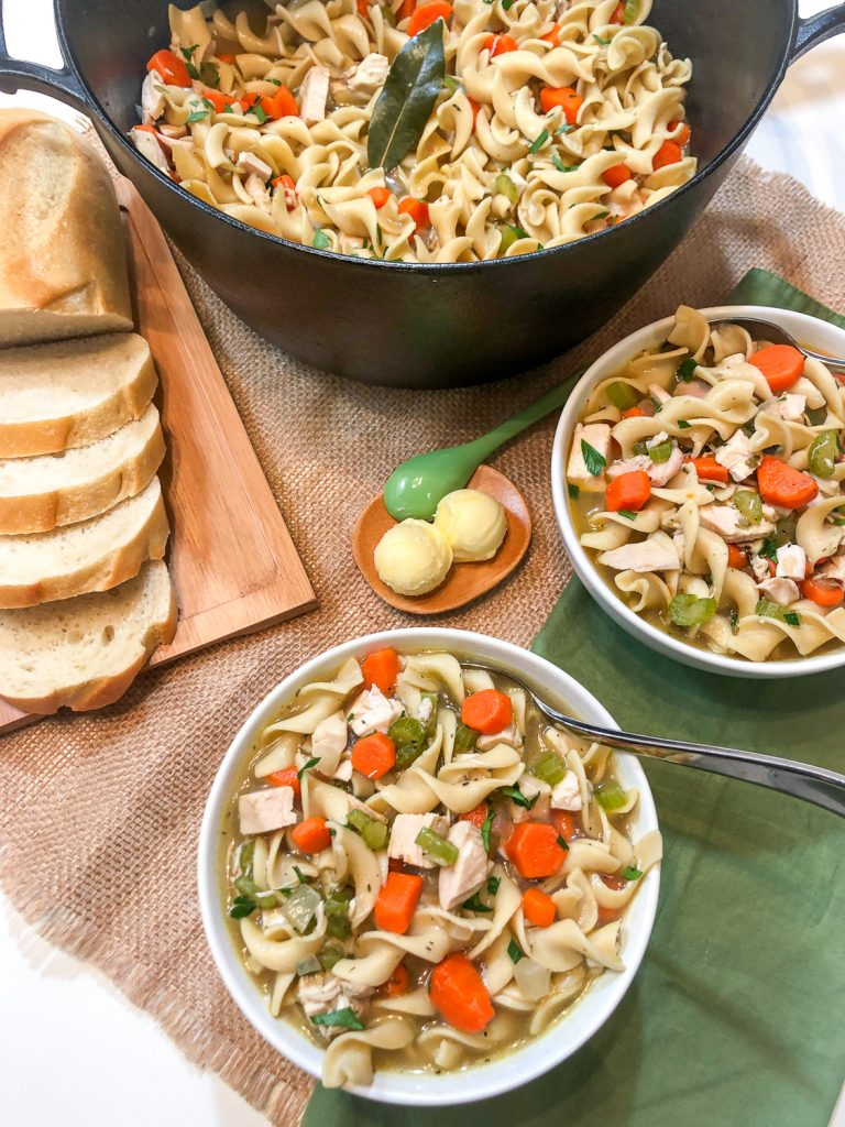 Two bowls of chicken noodle soup, sliced bread, butter, and the dutch oven.