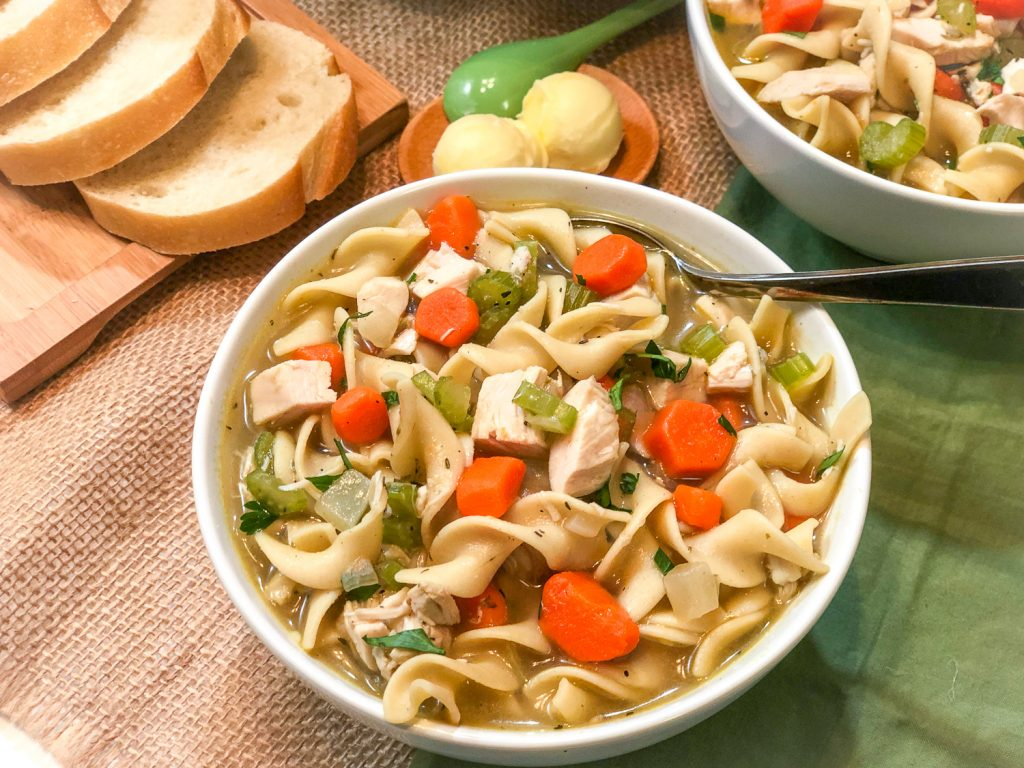 Bowl of chicken noodle soup with bread and butter in the background.
