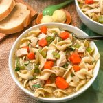 Bowl of chicken noodle soup with bread in the background.