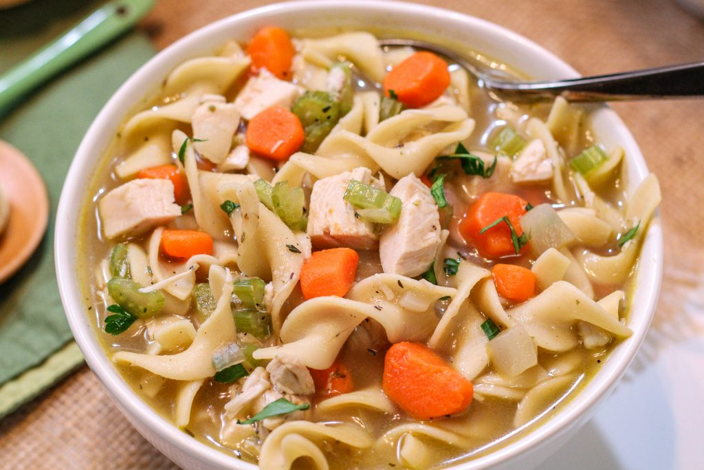 Close up shot of chicken noodle soup in a white bowl.