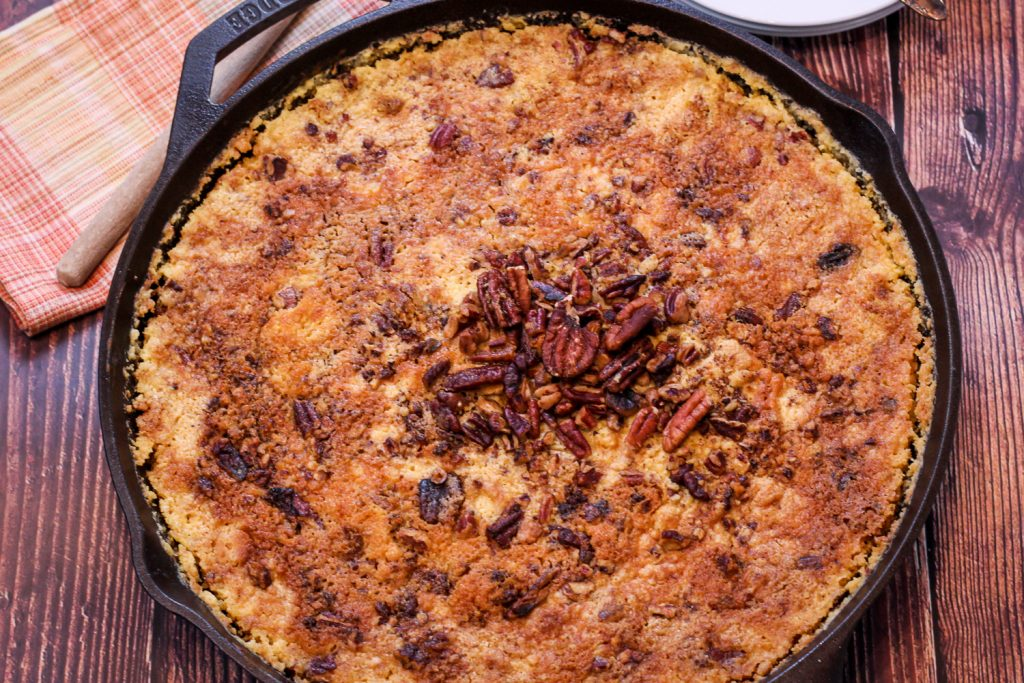 Close up image of baked pumpkin dump cake in a cast iron skillet.