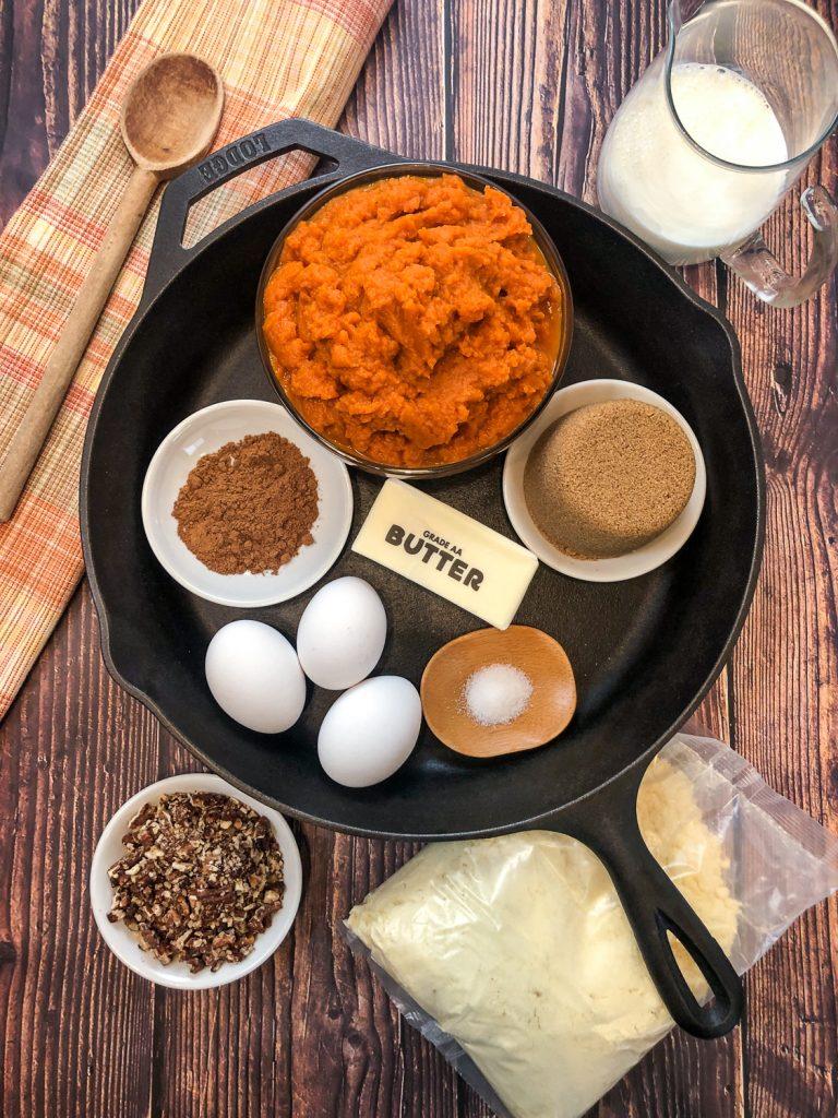Ingredients to make the dessert in a cast iron skillet: pumpkin puree, brown sugar, half and half, eggs, butter, salt, pumpkin pie spice, cake mix, and candied pecans.
