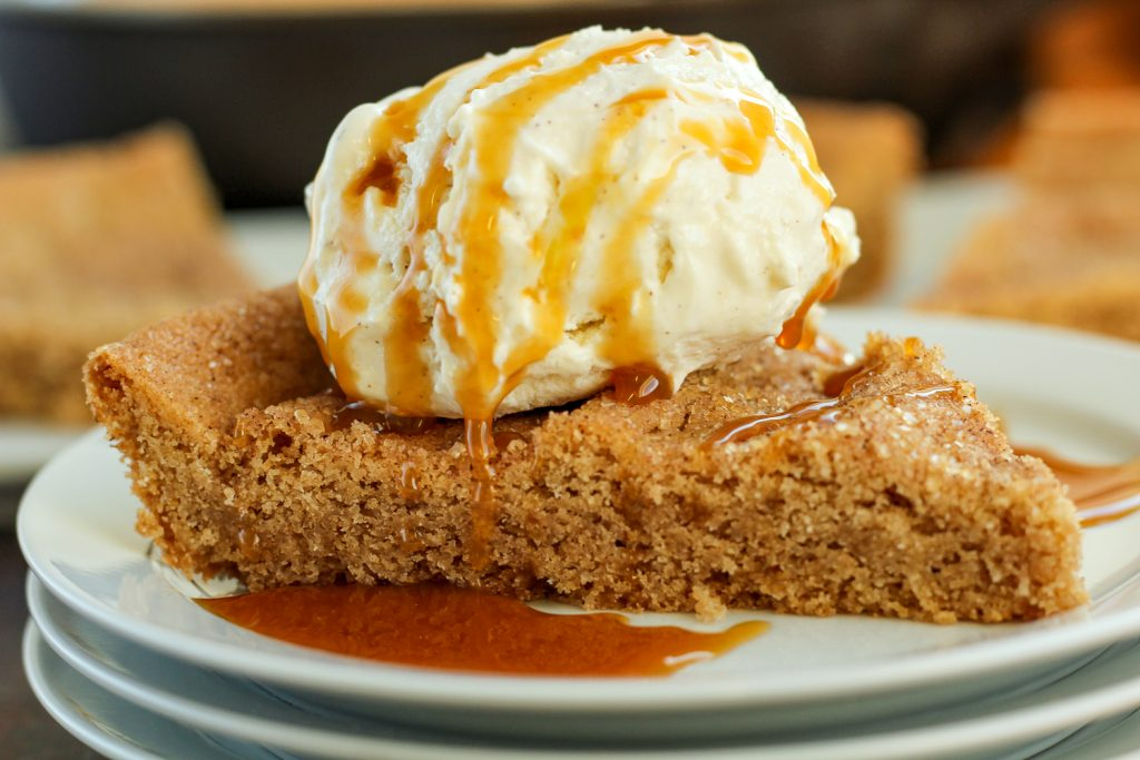 A slice of skillet snickerdoodle cookie on a white plate topped with a scoop of ice cream and caramel syrup.
