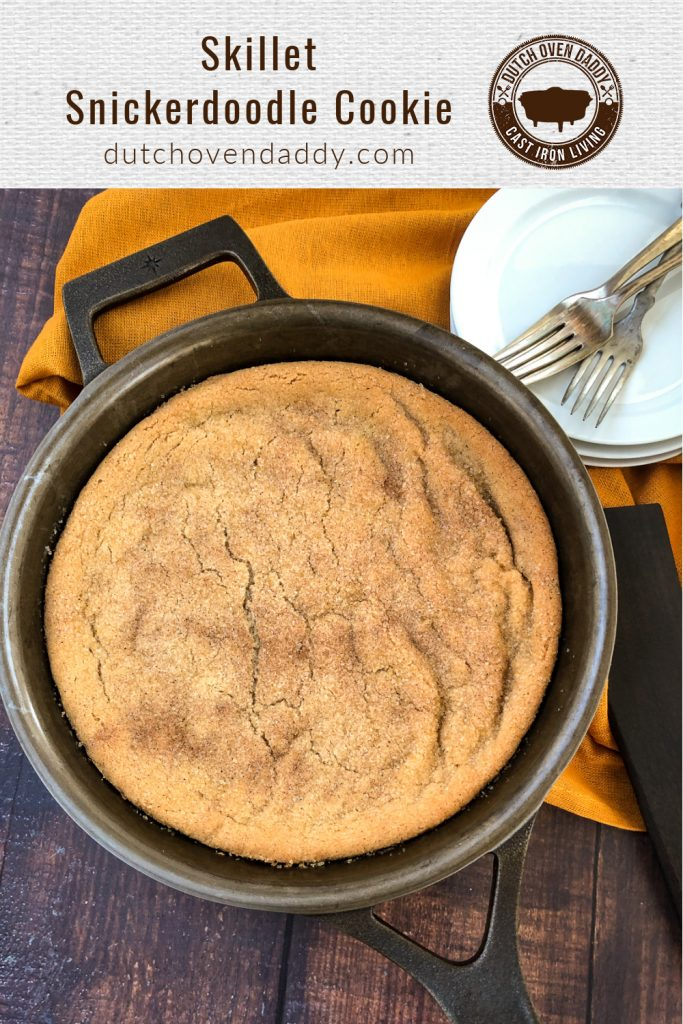 Branded image of a snickerdoodle cookie in a cast iron skillet.