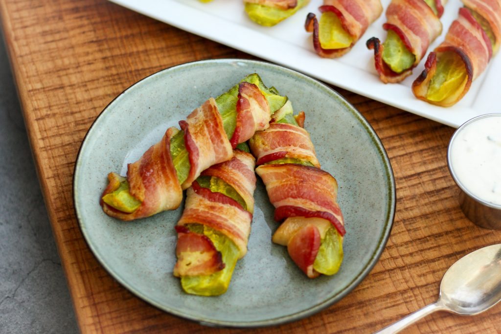 A plate of pickles wrapped in bacon.