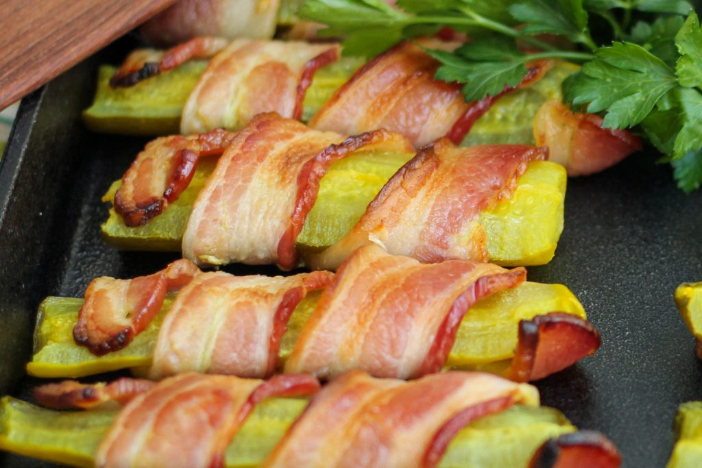 Close up of cooked and crisped bacon wrapped pickles.